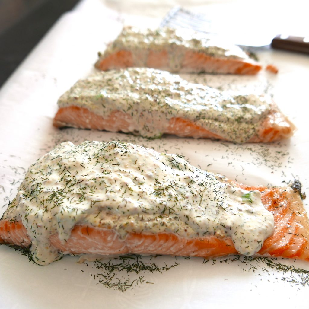 salmon with a creamy mustard dill sauce arranged on a white platter with fish spatula in background