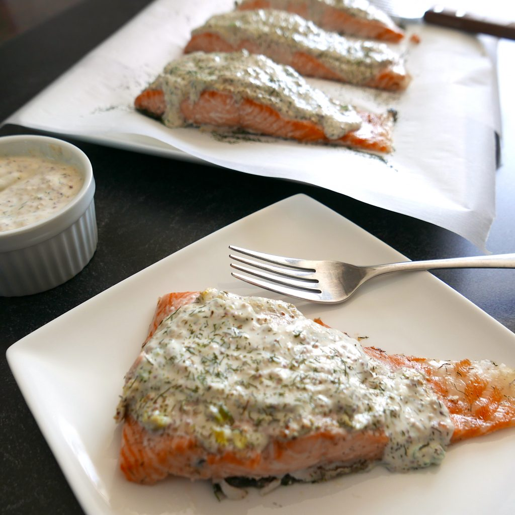 salmon with creamy mustard dill sauce on a white plate with fork and more salmon in background