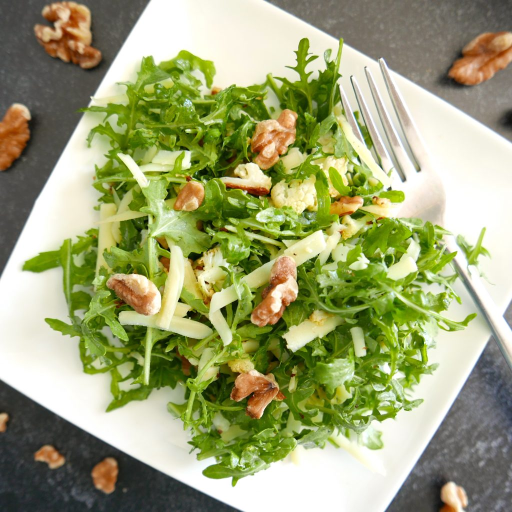 cauliflower salad with arugula, walnuts and cheese arranged on a white plate with silver fork