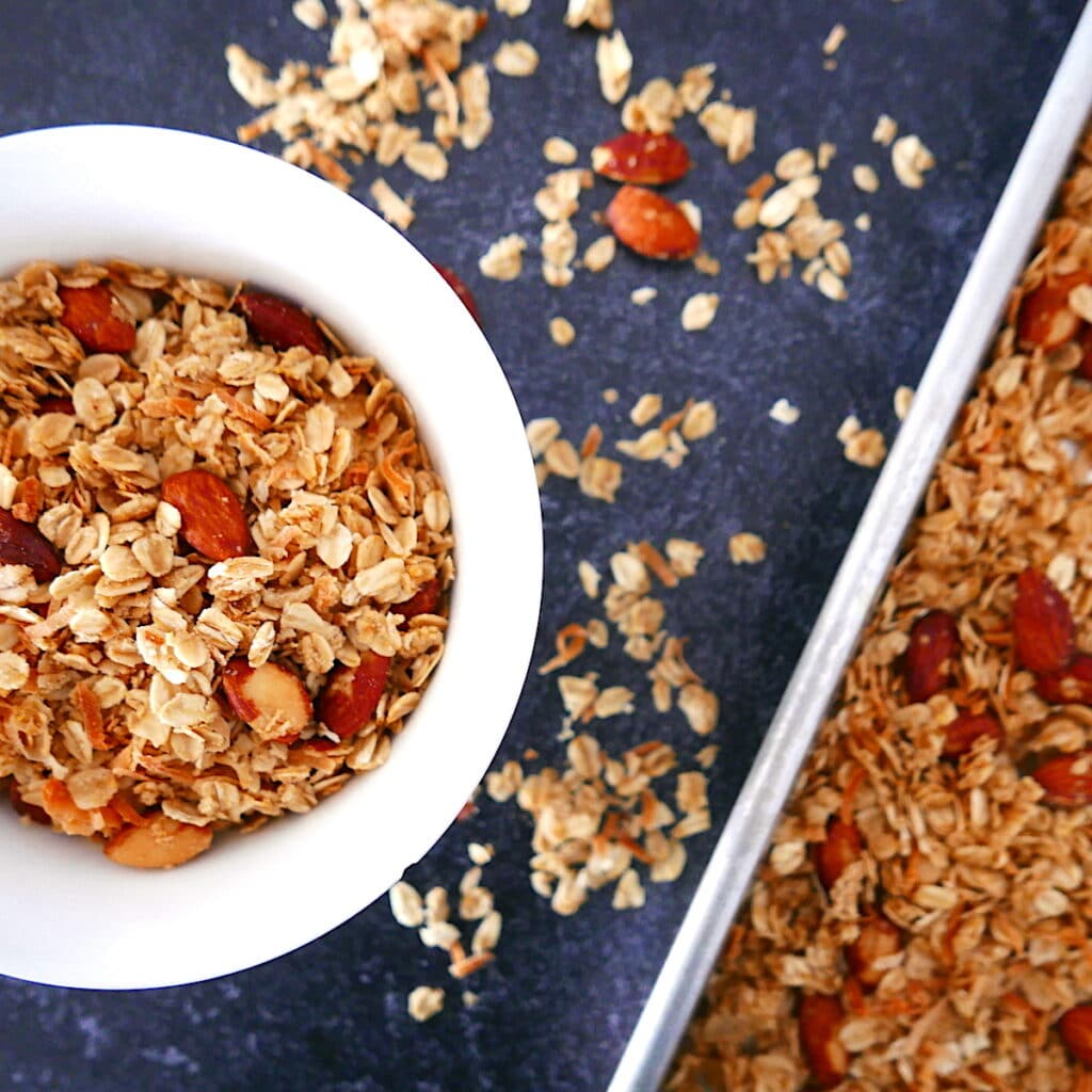 overhead shot of bowl of granola with pan of granola next to it