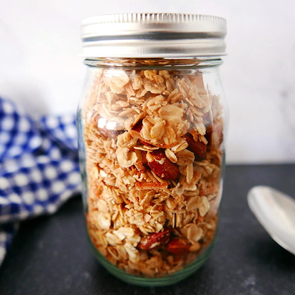 glass jar full of coconut granola with dish towel next to it