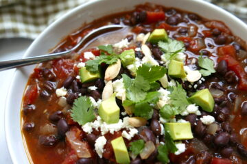 southwest black bean soup in a white bowl with spoon and garnished with cilantro and avocado