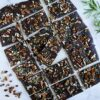 pecan rosemary chocolate bark cut into squares and arranged on marble table with rosemary sprigs in background