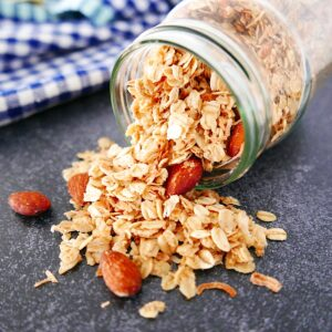 coconut almond granola spilling out of a tipped over mason jar