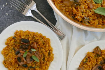 pumpkin and mushroom risotto on two white plates with pan in background and two forks