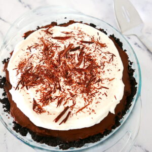 chocolate cream pie with oreo crust in a pie pan with server