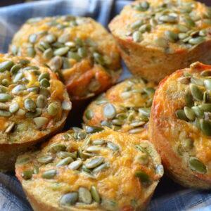 pumpkin cheddar muffins in a towel lined basket