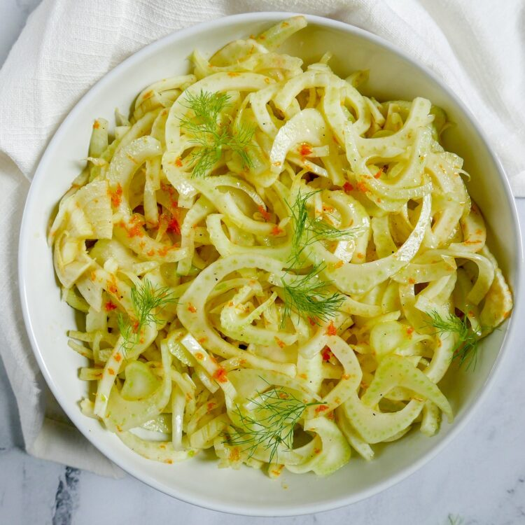 citrus fennel salad with fronds in a white bowl with white napkin