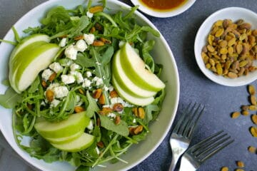 harvest apple salad in white bowl with cups of pistachios and dressing nearby