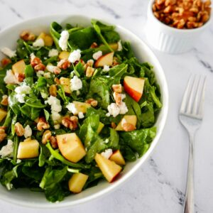 apple walnut goat cheese salad in white bowl