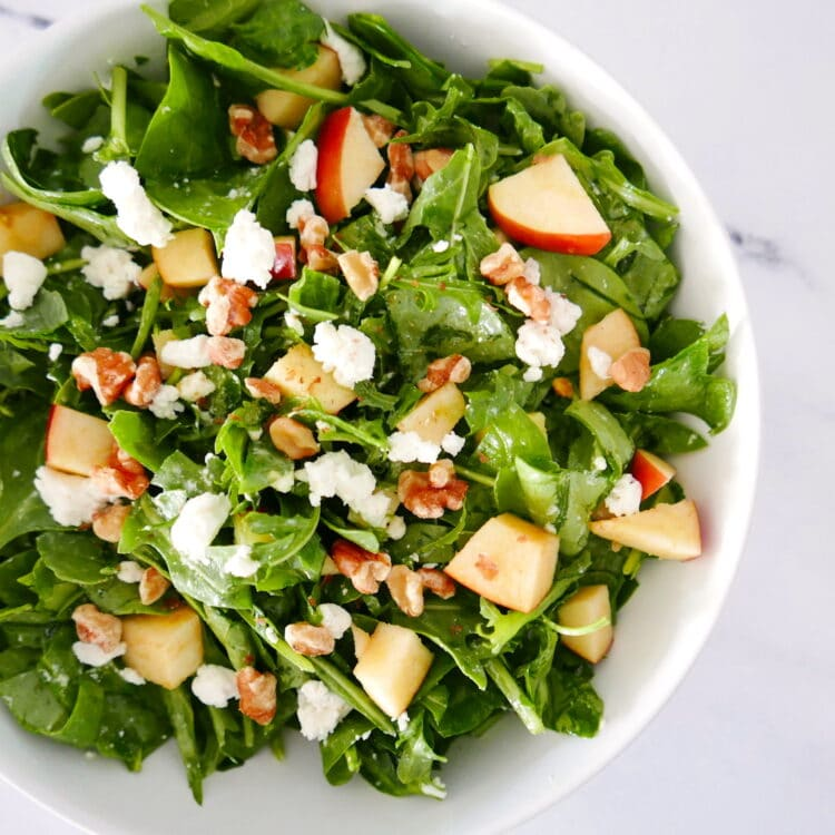 apple walnut goat cheese salad in a white bowl sitting on a marble counter