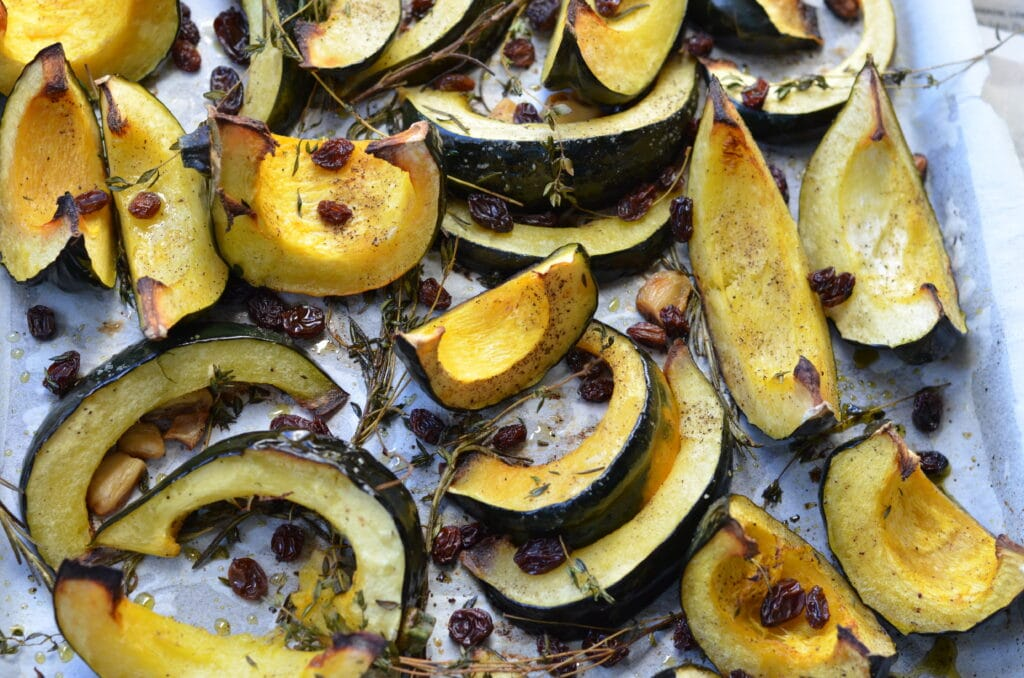 roasted acorn squash wedges with raisins and thyme arranged on a baking sheet