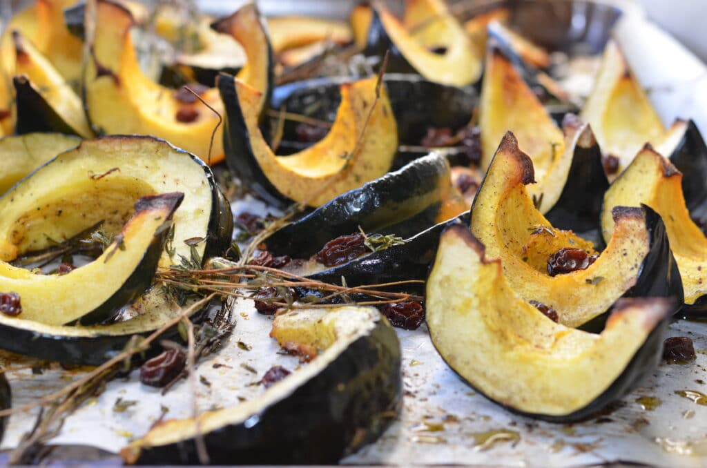roasted acorn squash wedges with raisins and thyme on a baking sheet