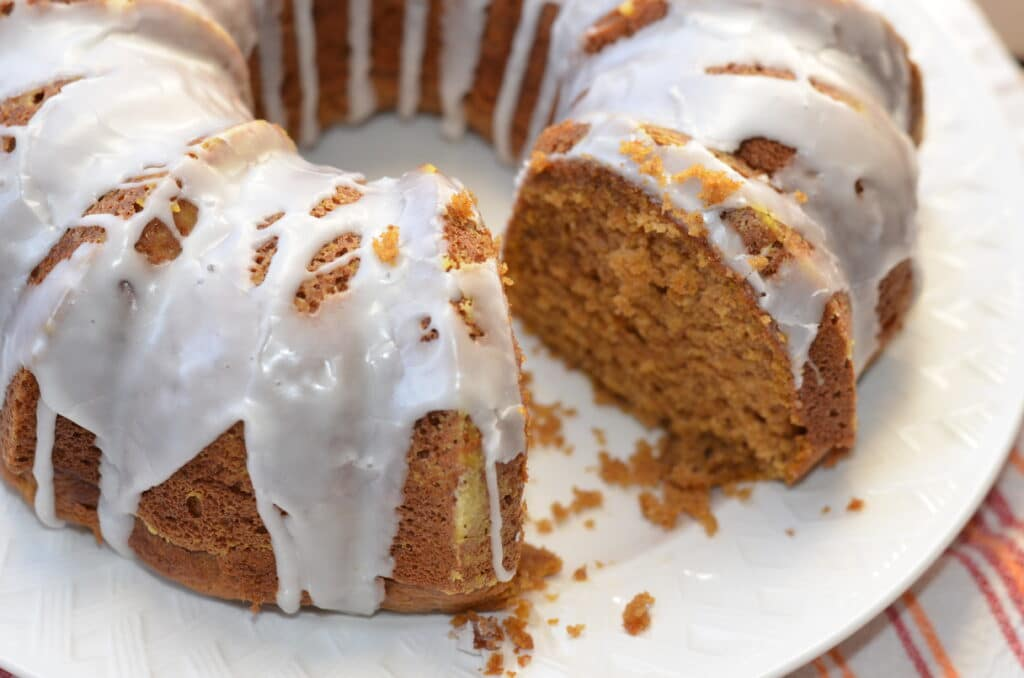 pumpkin spice bundt cake on a white platter with one piece missing