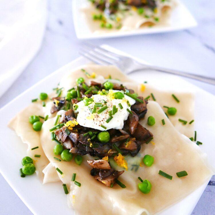 vegetarian pea ricotta ravioli on a white plate with white napkin