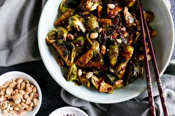 kung pao brussels sprouts in a white bowl with chopsticks next to a gray napkin