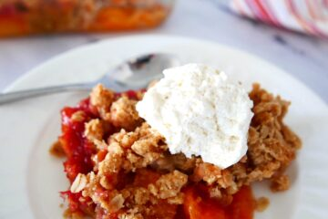 peach crisp with brown butter crumble on a white plate with a spoon and whipped cream and a pan of peach crisp in background