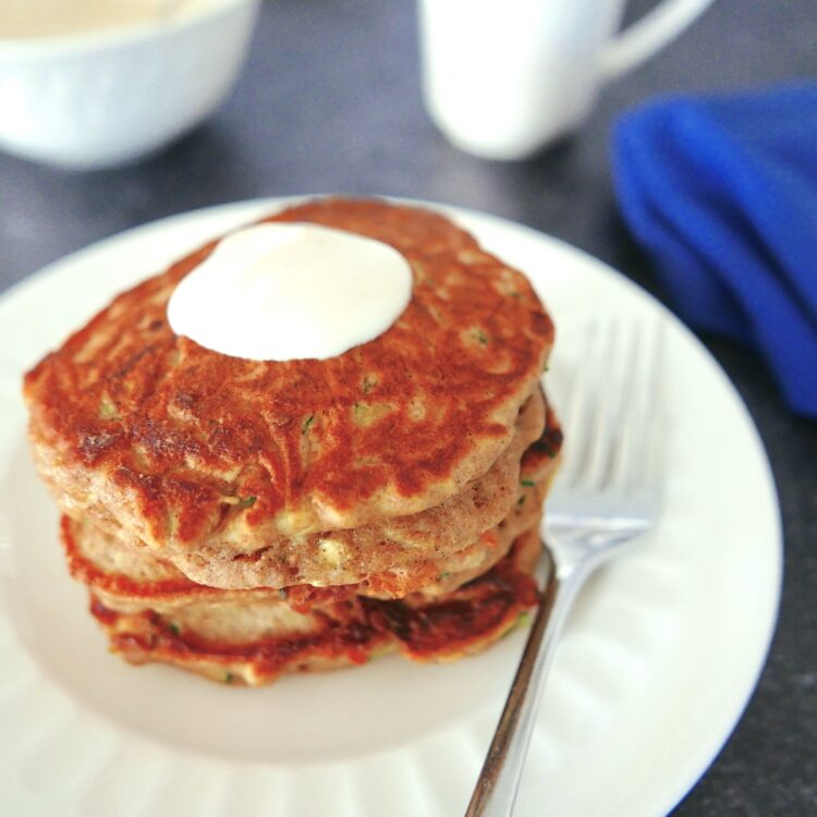 zucchini bread pancakes with maple yogurt sitting on a white plate with fork