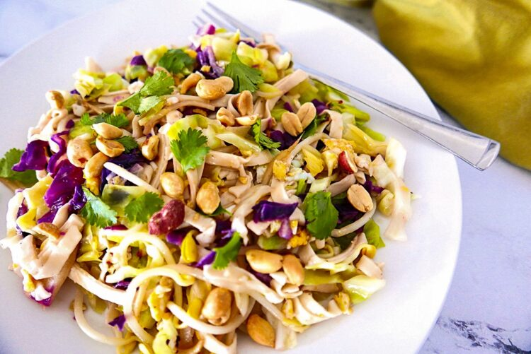 peanut pad thai on a white plate with fork and green napkin