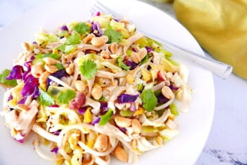healthy peanut pad thai on a white plate with fork