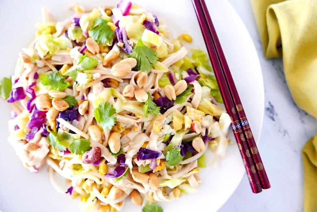 healthy peanut pad thai with chopsticks on a white plate