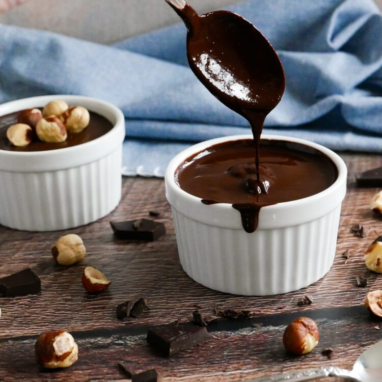 homemade vegan nutella in two white cups with spoon and hazelnuts