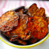 vegan eggplant chips in a yellow and white bowl on top of a pink napkin