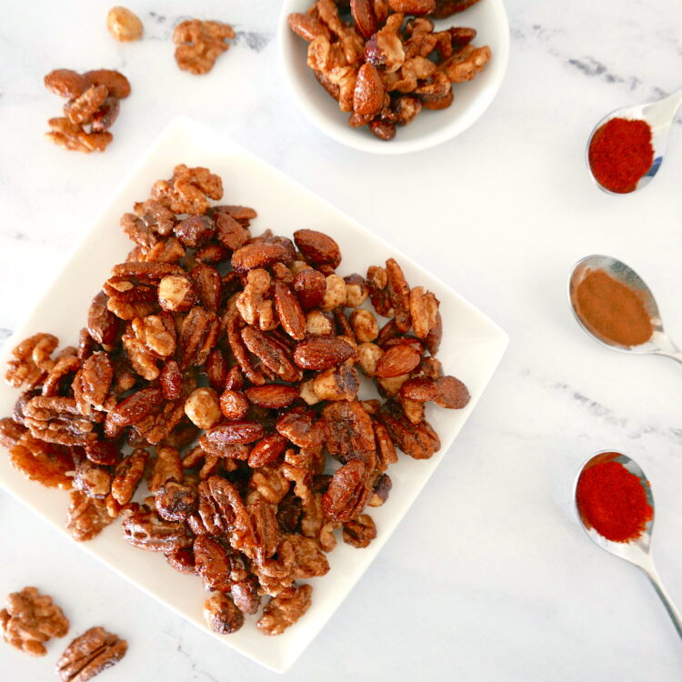 spiced candied nuts arranged on a white plate with nuts scattered around and three spoons full of spices nearby