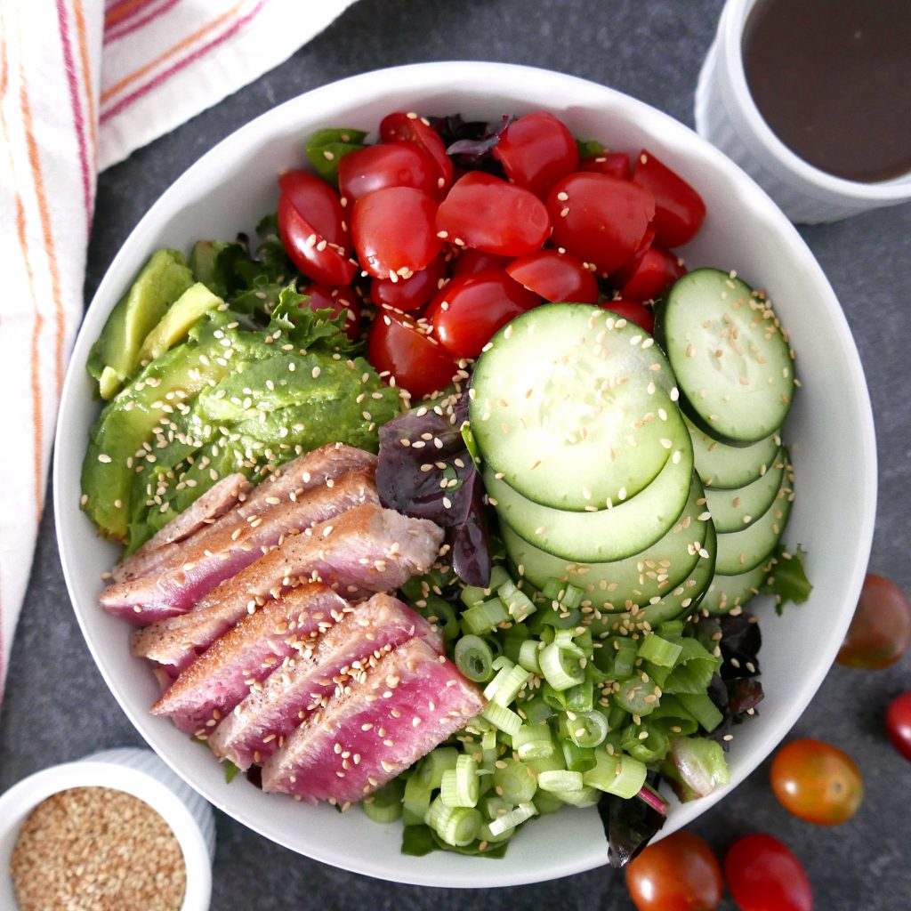 tuna steak salad with wasabi vinaigrette in a large white bowl sitting on a marble counter top