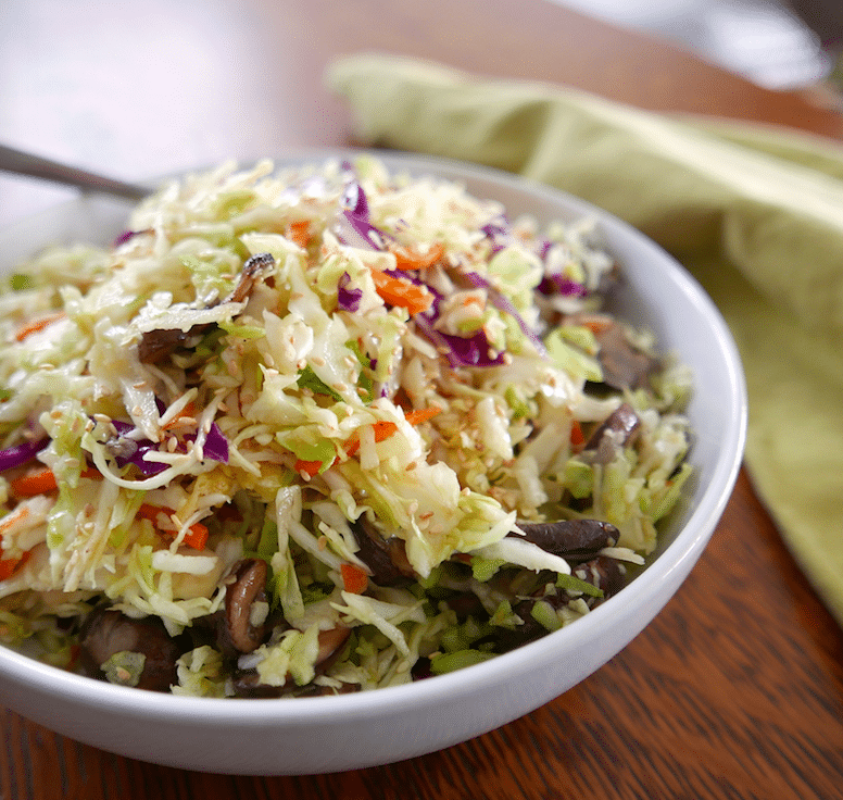 miso coleslaw in a white bowl with green napkin next to bowl