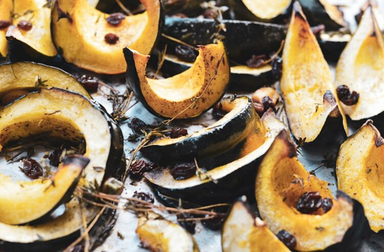 roasted acorn squash with thyme on a baking sheet