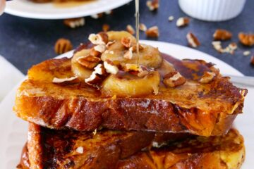 caramelized bananas french toast on a white plate with maple syrup