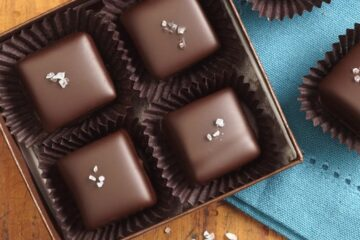 four sea salt caramels in a brown box on top of a blue place mat