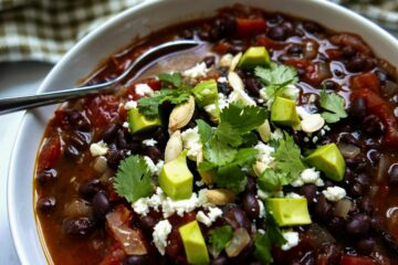 southwest black bean soup with spoon in a white bowl