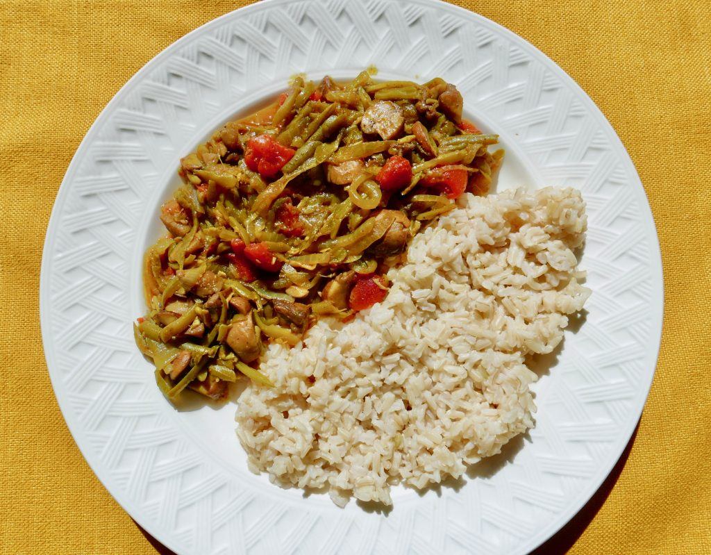 green bean and mushroom curry with brown rice arranged on a white plate