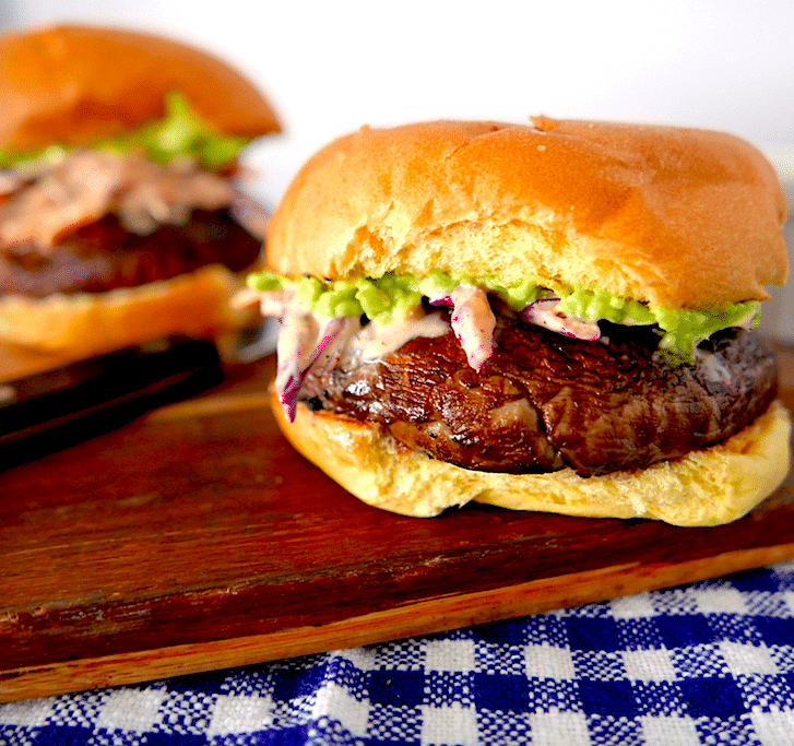 two portobello burgers sitting on a wooden cheese board