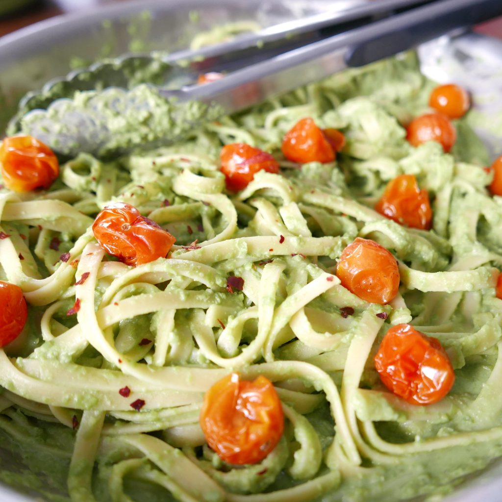 silver saute pan full of pesto vegan pasta & red roasted tomatoes, with silver tongs in background