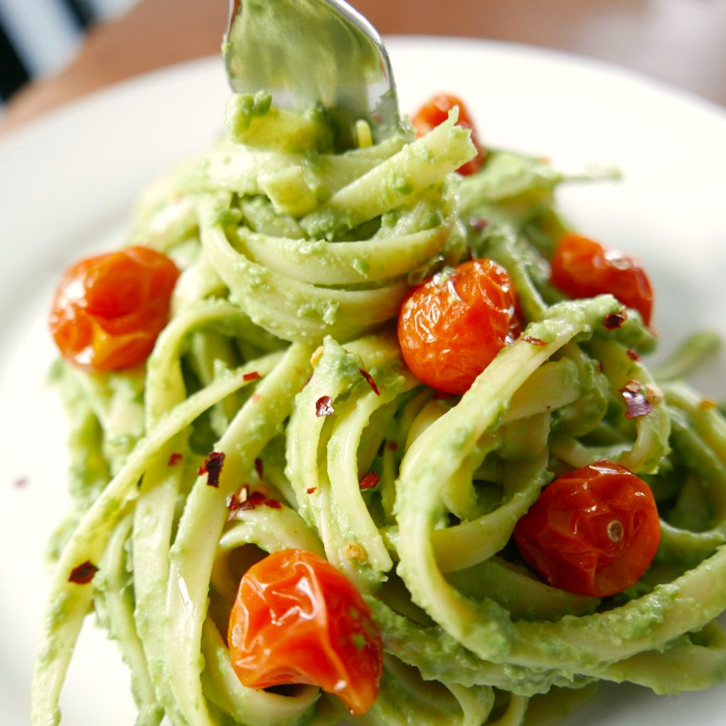pesto vegan pasta with red roasted tomatoes being spooled around a silver fork and sitting on a white plate