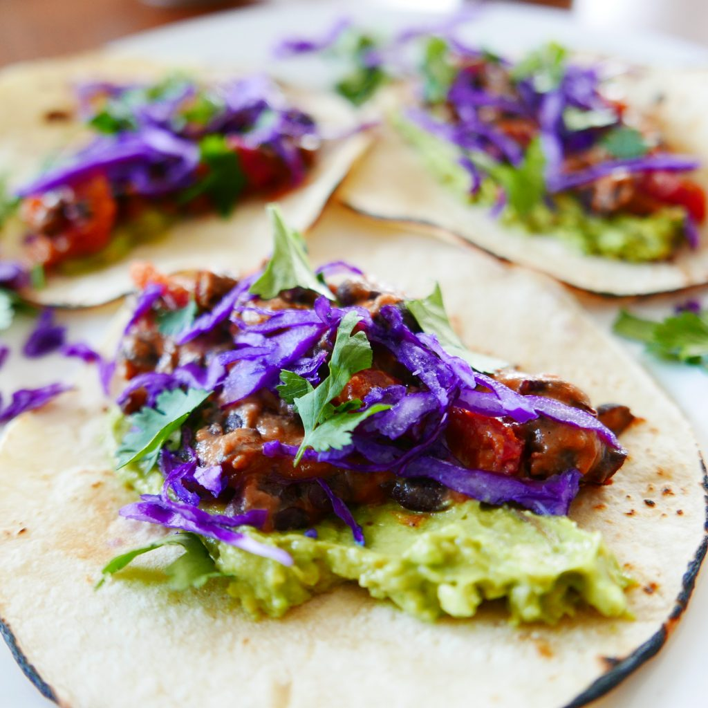 close up of three black bean and cheese tacos garnished with smashed avocado, shredded red cabbage and green cilantro.