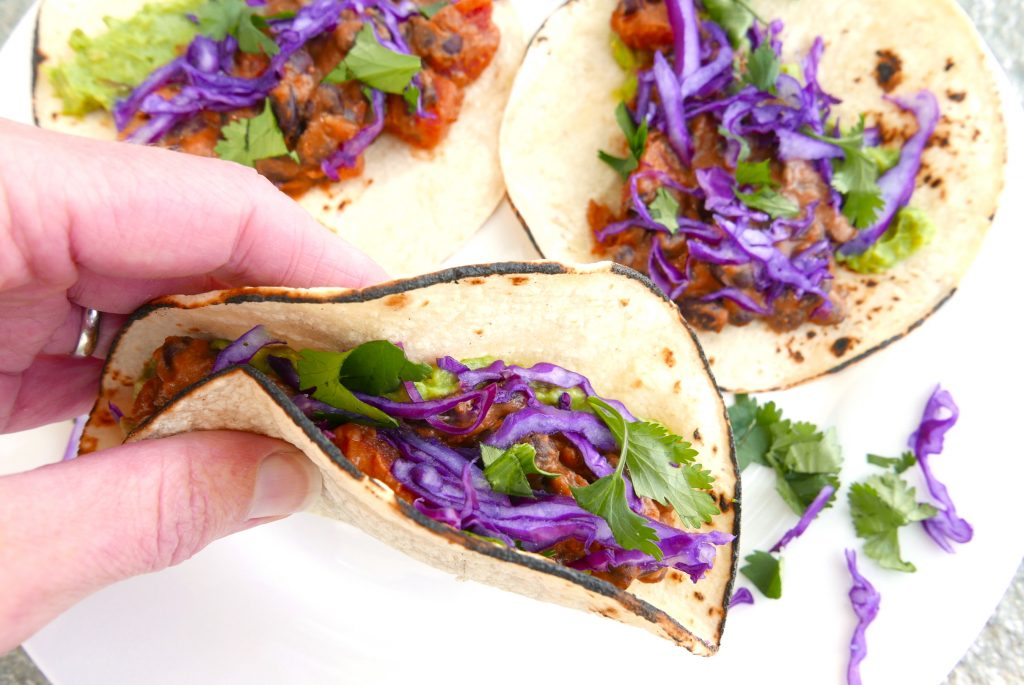 white hand holding folded black bean and cheese taco with red cabbage and green cilantro. Two additional tacos are in the background sitting on a white plate.