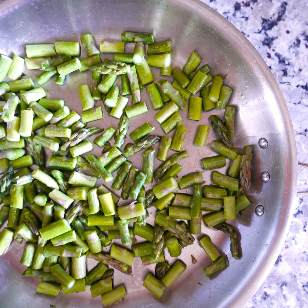sauteed asparagus in a silver frying pan