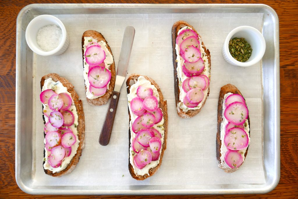 five pieces of roasted radish and herbed ricotta sourdough toasts sitting on a baking sheet, with chives and sea salt