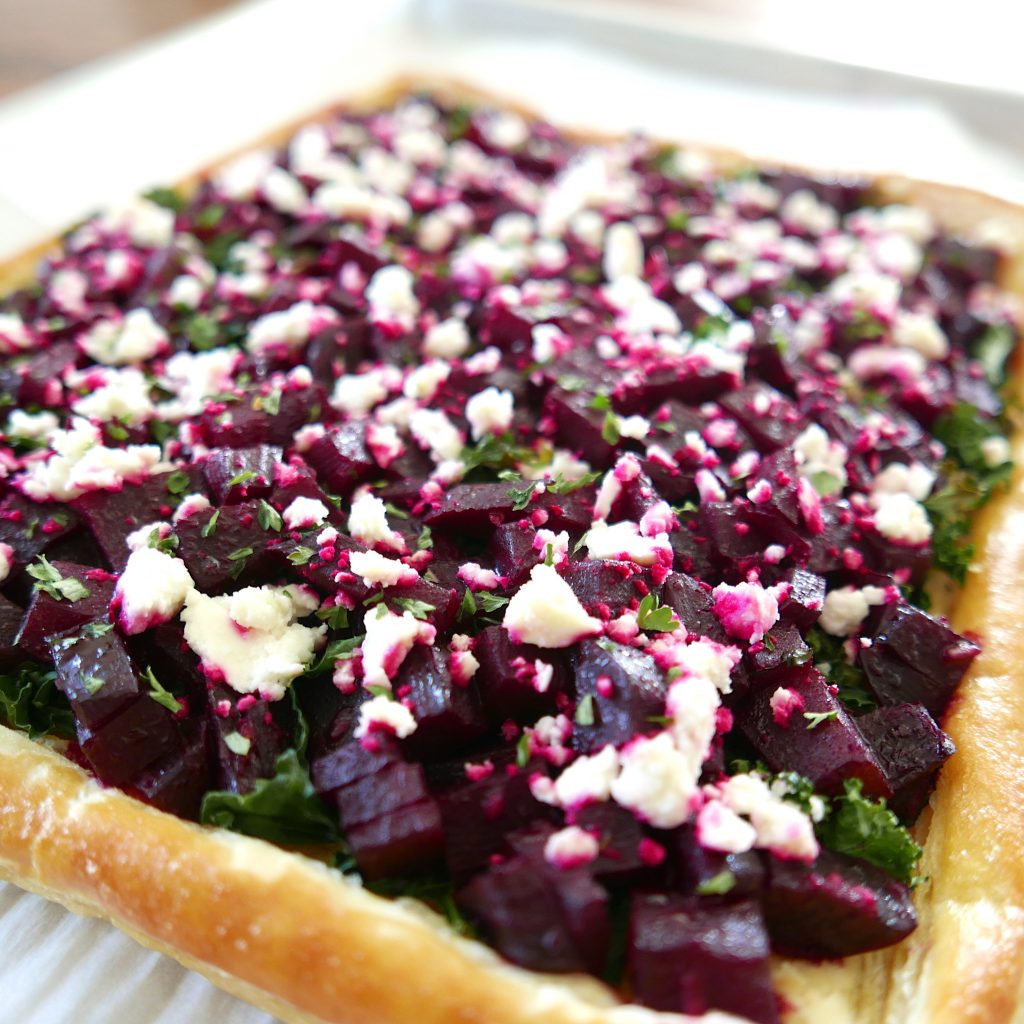 roasted beetroot tart with feta and kale on a baking sheet