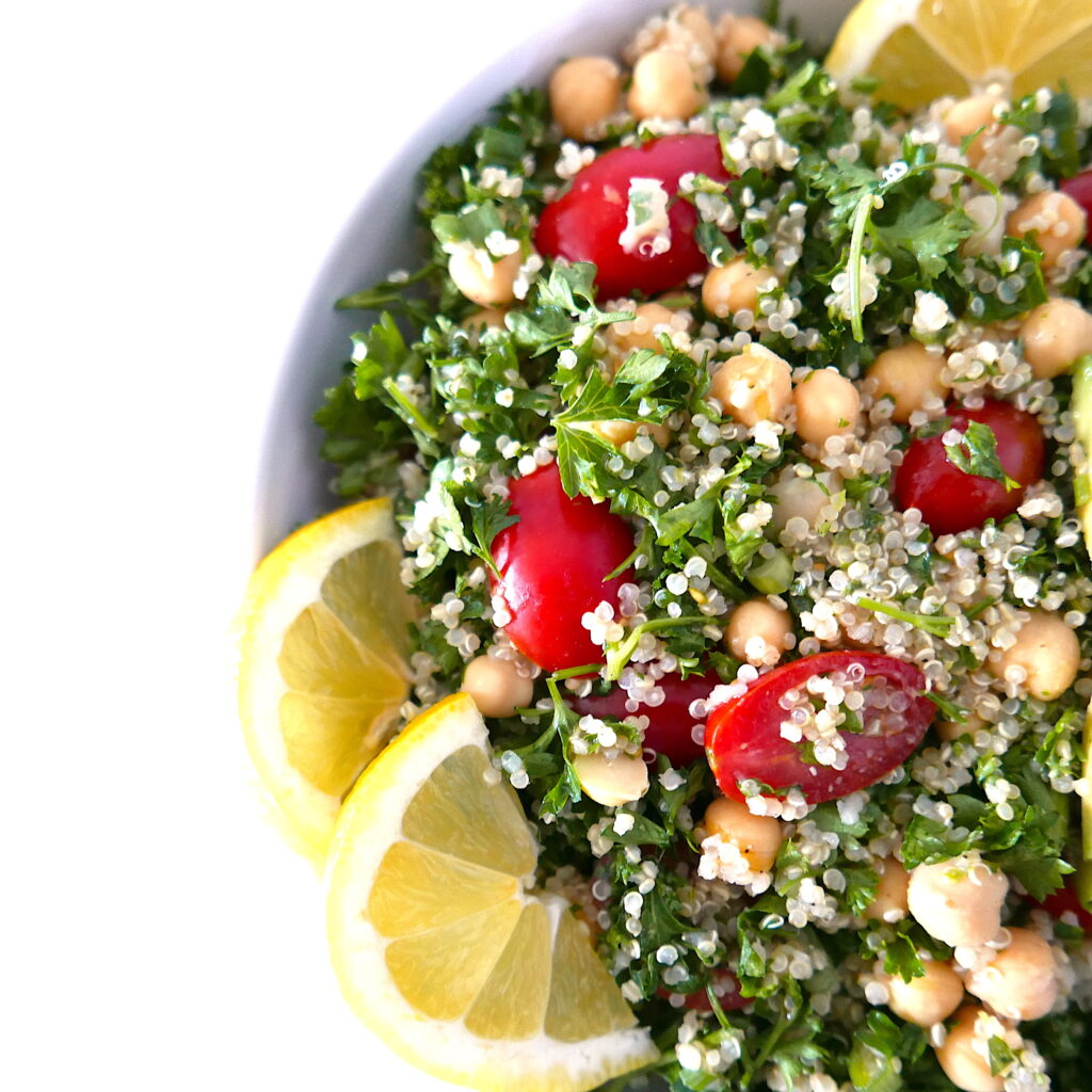 close up of quinoa tabbouleh salad with chickpeas and avocado in a white bowl with lemon wedges on top sitting on a white table