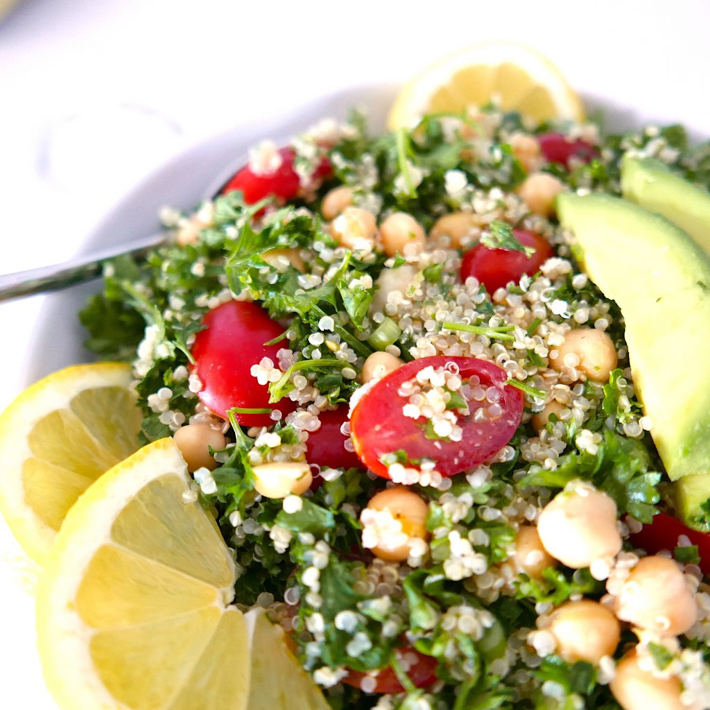 close up of quinoa tabbouleh salad with chickpeas and avocado in white bowl with silver spoon in bowl