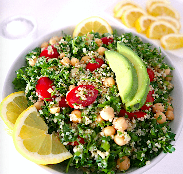 quinoa tabbouleh salad with chickpeas and avocado in a white bowl with a plate of lemon wedges in the background