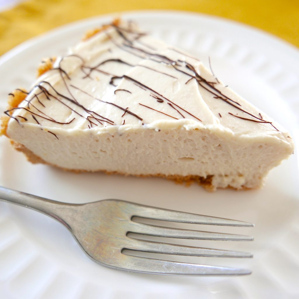 one piece of no-bake tahini cheesecake sitting on a white plate on top of a mustard-colored place mat