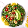 quinoa tabbouleh salad with chickpeas and avocado in a white bowl with lemon slices placed on the side