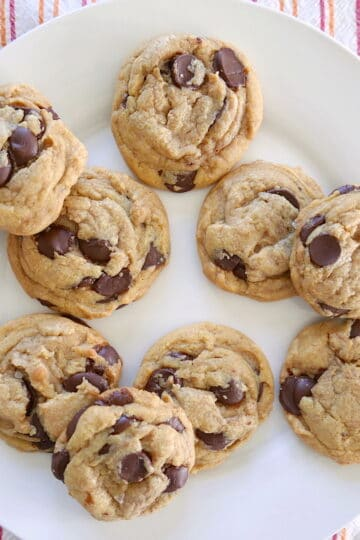 brown butter chocolate chip cookies arranged on a white plate with pink napkin underneath