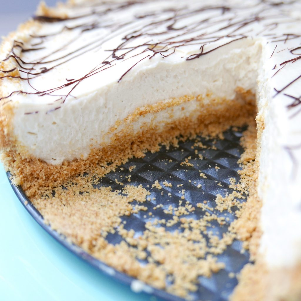no bake tahini cheesecake on a plate with one piece missing